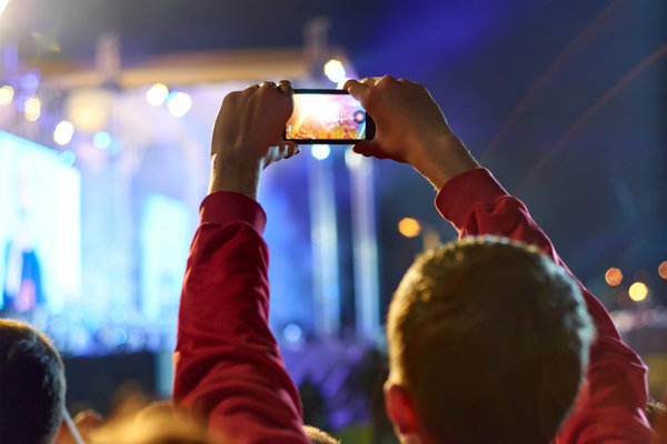 A man records a performer on his smartphone